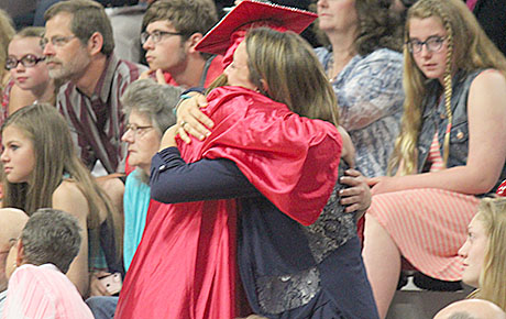 Graduates received hugs from family and friends during the presentation of flowers to their parents.