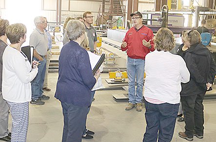Clyde Stuhr (in red shirt) conducts a tour of the Sentinel Building Systems plant.