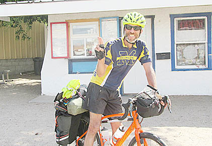 Cross-country bicyclist Amos Kornfeld leaving Shorty's Ice Cream Shoppe in Albion last Thursday.