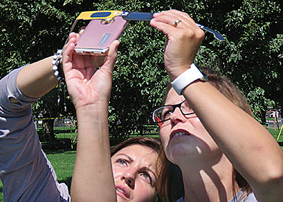 Abbie Nelson, l., and Jackie Herley, r., used their eclipse glasses as a filter while taking pictures with their phones.