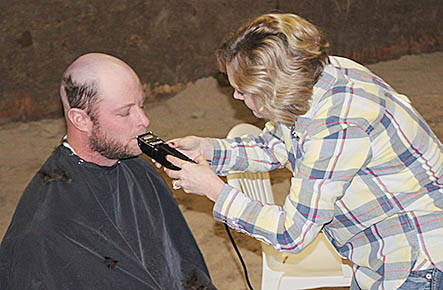 Wes Stokes gets a close shave from his wife, Jenna, during the fundraiser last Saturday.