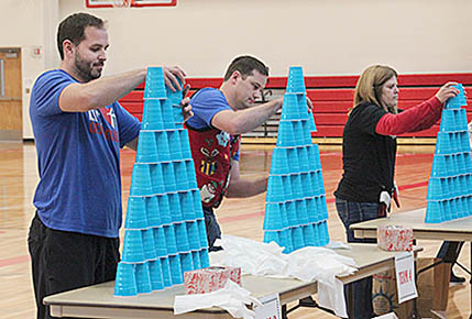 Teachers Justin Harris and Justin DeWitt, and aide Michelle Merten competed in the timed cup-stacking event.