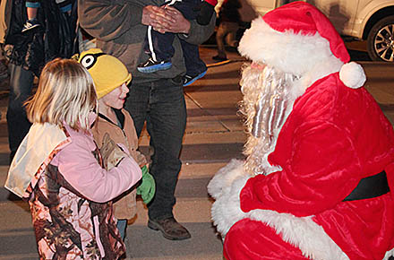Youngsters visit with Santa outside the Veterans Club.