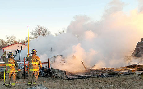 Albion firemen watch the smoldering remains of a barn at the Jim Staub farm early Monday morning. -- Albion Fire & Rescue Photo