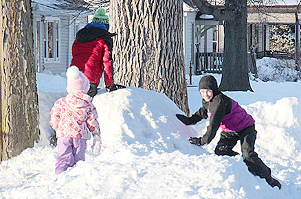 Local youngsters play on a mound of snow along Sixth Street Tuesday afternoon.